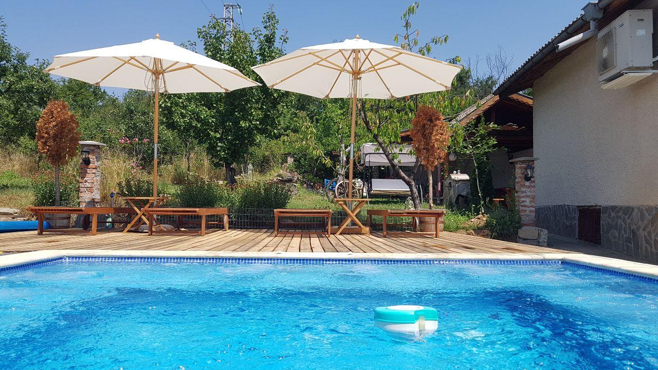 Дневен поглед към зоната за релакс, шезлонгите, барбекюто, градината от басейна на къща за гости Каса Роса Кюстендил